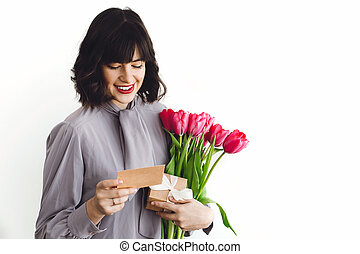 Beautiful brunette girl holding bouquet of tulips, gift box and greeting card on white background indoors, space for text. Happy young woman with flowers. Happy mothers day.