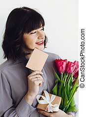 Beautiful brunette girl holding bouquet of tulips, gift box and greeting card on white background indoors, space for text. Happy young woman with flowers. International womens day