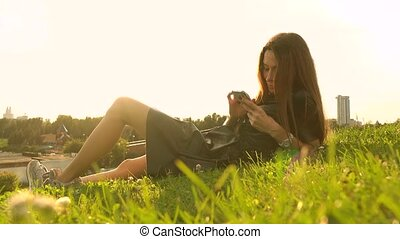 Beautiful brunette girl in black dress using her smartphone on the lawn. Leisure time. 4K video