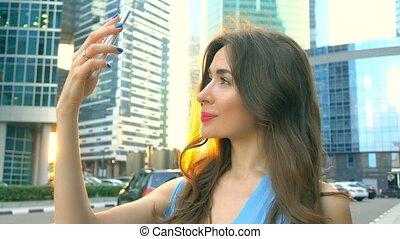 Beautiful brunette girl in blue dress making selfie at sunset against skyscrapers. 4K clip
