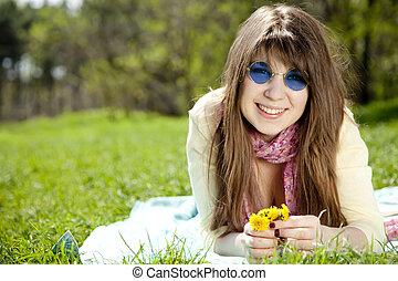 Beautiful brunette girl in blue glasses at the park.