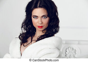 Beautiful Brunette Girl in fur coat over modern interior white background