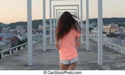 Beautiful brunette girl in orange t-shirt and shorts runs...
