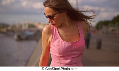 Beautiful brunette girl in pink dress standing on Moscow river embankment. Slow motion steadicam clip