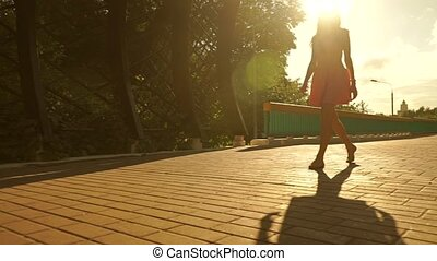 Beautiful brunette girl in pink dress walking though garden arched passage against blazing sun. Steadicam shot
