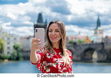 girl in red dress make a selfie in Prague