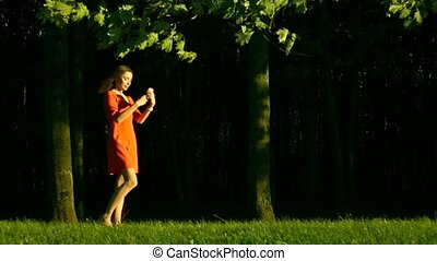 Beautiful brunette girl in red dress making photo wit her mobile phone in the park. Slow motion video