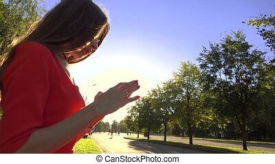 Beautiful brunette girl in red dress using her smartphone in the park. 4K video