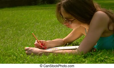 Beautiful brunette girl in sunglasses laying on the grass and drawing. 4K steadicam shot