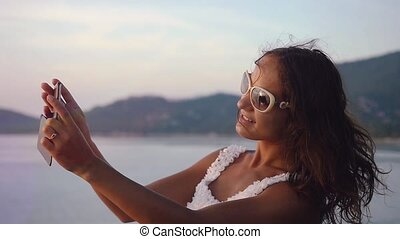 Beautiful brunette girl in sunglasses takes photos of sunset on mobile phone camera. slow motion. 1920x1080