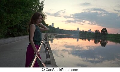 Beautiful brunette girl looking at sunset river on park embankment. Slow motion shot