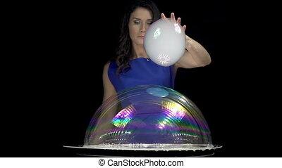 Beautiful brunette girl mixing soap bubbles