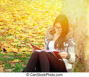 Beautiful brunette girl reading book in nature