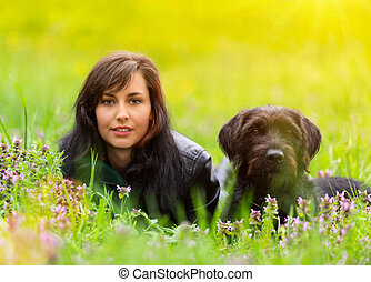 Beautiful brunette girl sitting in grass with her funny black dog.