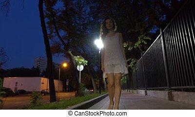 Beautiful brunette girl walking at camera on night street steadicam 4K shot