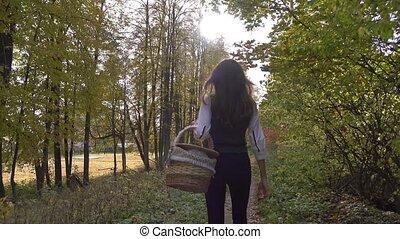 Beautiful brunette girl walking through autumn woods holding...