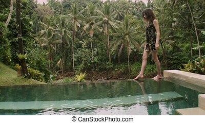 Beautiful brunette girl walks along of the edge of pool