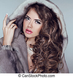 Beautiful brunette girl wearing in mink fur coat with long hair styling isolated on grey background. Fashion winter woman model posing.