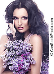 Beautiful brunette girl with a gentle romantic make-up, pink lips and flowers. The beauty of the face.