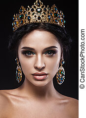 Beautiful brunette girl with a golden crown, earrings and professional evening make-up. Beauty face.