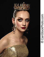 Beautiful brunette girl with a golden crown, earrings and professional evening make-up