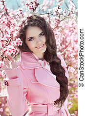 Beautiful brunette girl with braided hair over pink blossom tree, outdoors portrait