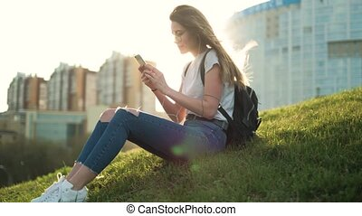 Beautiful brunette girl with glasses sits in a park on the grass at sunset listening to music on headphones and looks something in the phone