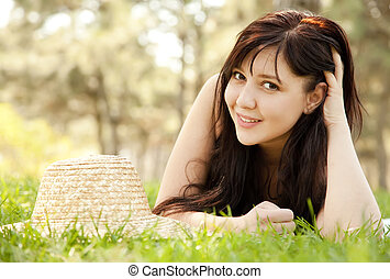 Beautiful brunette girl with hat at the park.