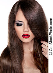 Beautiful Brunette Girl with Healthy Long Hair and Red Lips.  Fashion Model Woman touching her Long and Healthy Brown Hair. Isolated on white background.
