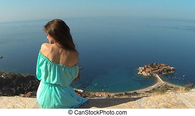 Beautiful brunette Girl with Healthy Long Hair relaxing on rock above island and city. Outdoors. Happy Young Woman Enjoying Nature and having Fun over sea and blue sky. Sveti Stefan, Montenegro.