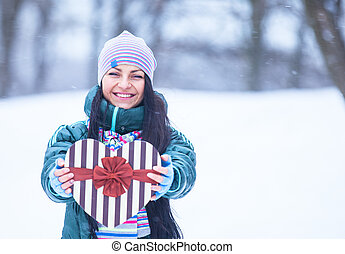 Beautiful brunette girl with heart shape box in the winter park.