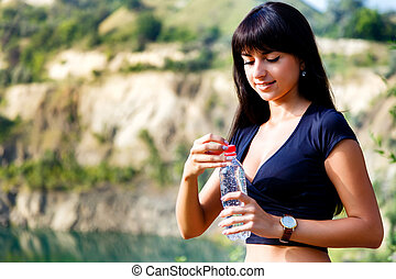 Beautiful brunette girl with long hair holding a bottle of water into the mountains