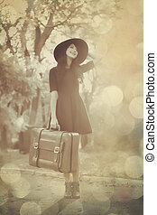 Beautiful brunette girl with suitcase in the park.