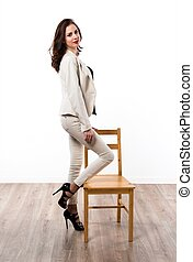 Beautiful brunette girl with wooden chair