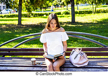 beautiful brunette girl young girl student sitting on a park bench reading a paper book with a cup stock photo csp35646141