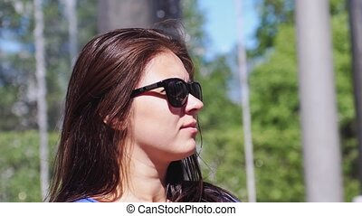 Beautiful brunette happy woman in sunglasses enjoying the sunlight smiles on nature in slow motion. 1920x1080