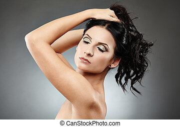 Beautiful brunette holding her hair up with eyes closed