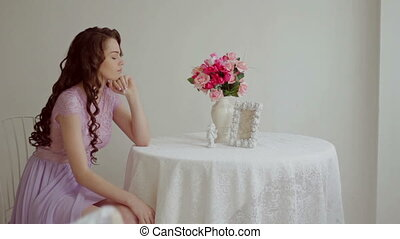 Beautiful brunette in a pink dress sits at a table in a beautiful studio