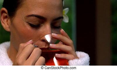 Beautiful brunette in bathrobe drinking tea