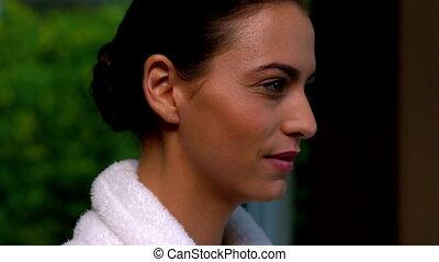 Beautiful brunette in bathrobe smil