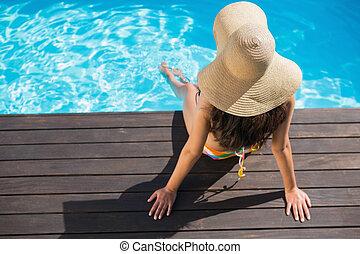 Beautiful brunette in bikini sitting by the pool paddling on...