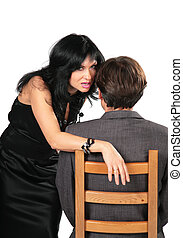 Beautiful brunette in black dress whispers on ear man sitting on chair