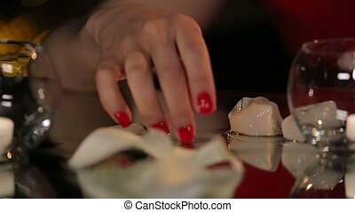 Beautiful Brunette in Red Dress Playing with a Candle and Melting Ice Cubes on the Mirror Table