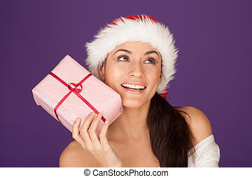 Beautiful brunette in Santa hat with gift