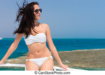 Beautiful brunette in swimsuit standing on the yacht at a...
