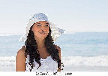 Beautiful brunette in white sunhat looking away