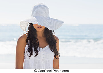 Beautiful brunette in white sunhat looking down