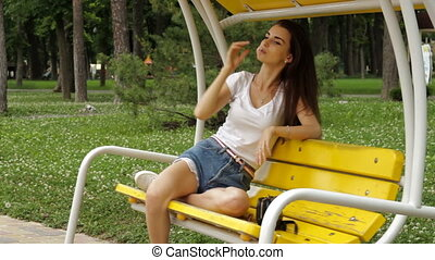beautiful brunette is resting on a swing and sucks a yummy...