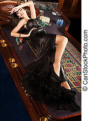 Beautiful brunette lies on table in casino - Beautiful...