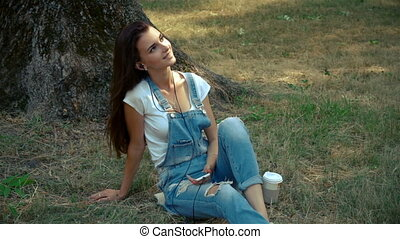 beautiful brunette listens to music with headphones while sitting on the grass